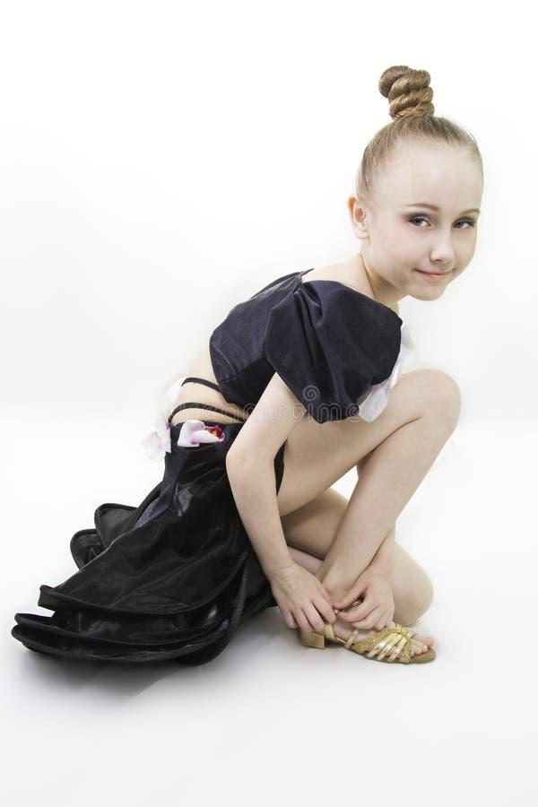La ragazza di dancing si è seduta per clasp un pattino fotografia stock libera da diritti