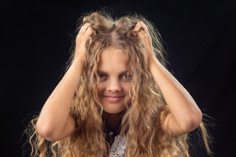 La ragazza di dieci anni stringe le mani con capelli biondi lunghi fotografia stock libera da diritti