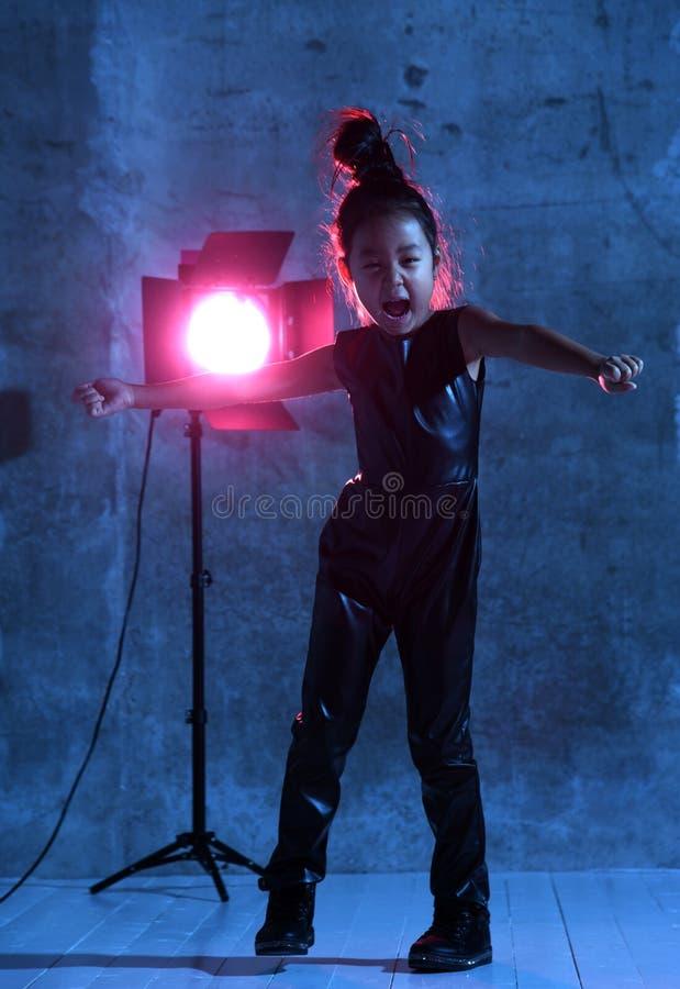 La ragazza di modello asiatica di alta moda con il riflettore dello studio variopinto compone cheerful immagine stock