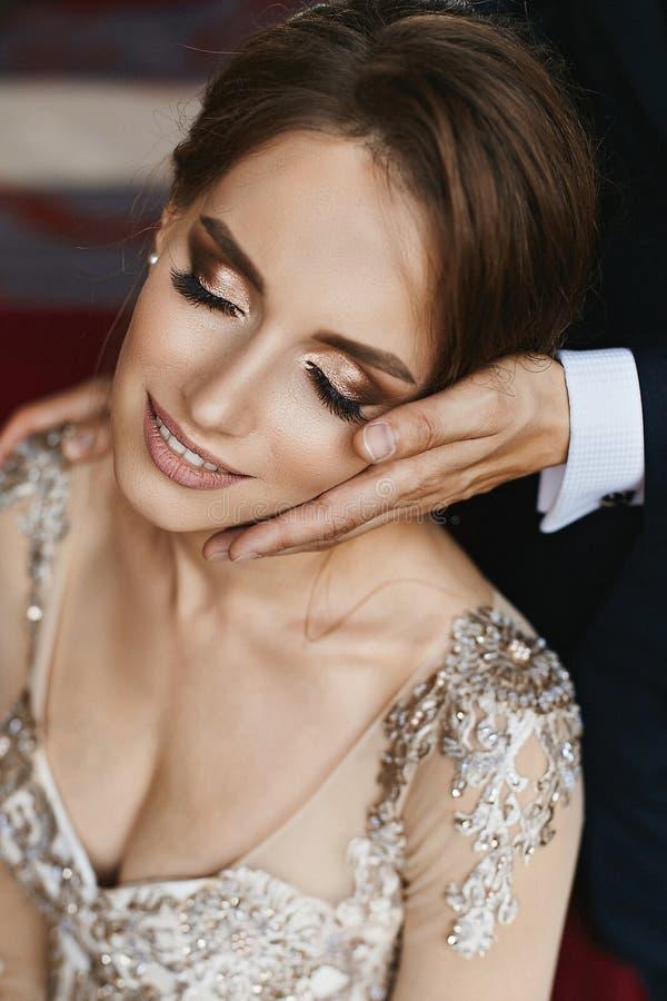 La ragazza di modello castana alla moda e bella con l'acconciatura di nozze ed il trucco luminoso in vestito alla moda dal pizzo  fotografia stock libera da diritti