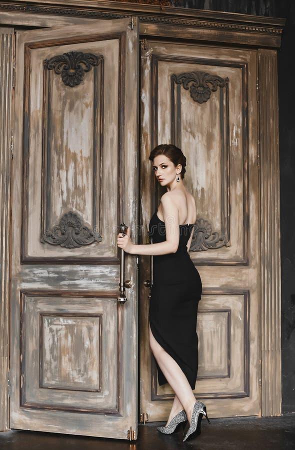 La ragazza di modello castana sexy con un taglio di capelli d'avanguardia e con trucco luminoso, in un vestito lungo nero alla mo immagini stock libere da diritti