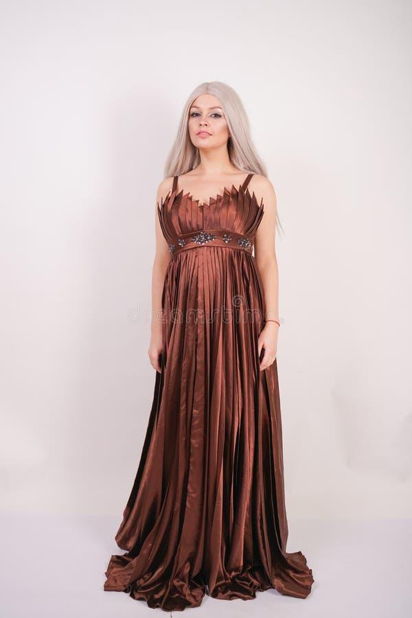 La ragazza di modello caucasica bionda di lusso in vestito da sera lungo di colore del cioccolato ha fatto di tessuto pieghettato fotografia stock