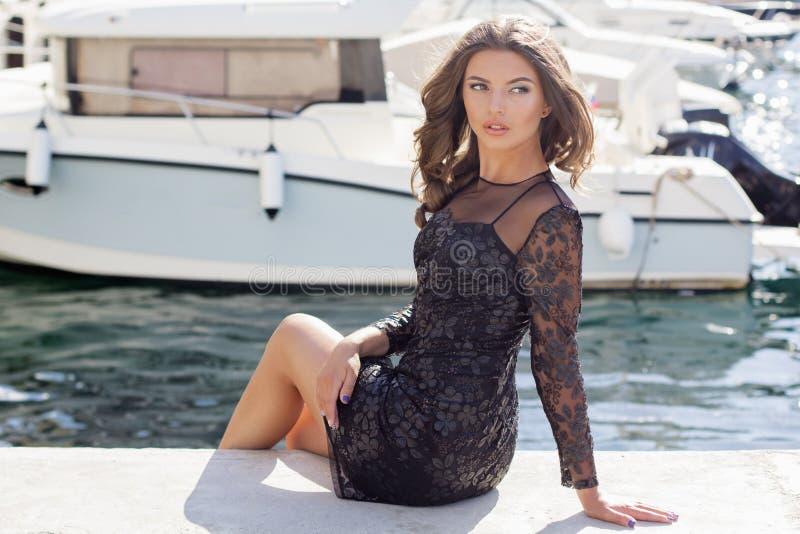 La ragazza di modo sta sedendosi vicino agli yacht immagini stock libere da diritti