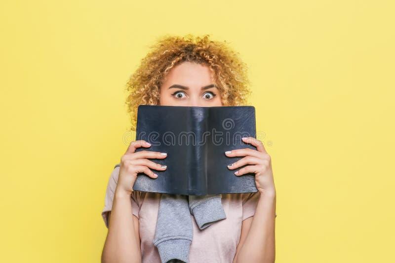 La ragazza di Mysterical sta riguardando la sua parte bassa del fronte di taccuino in copertura scura Sta considerando la macchin fotografia stock
