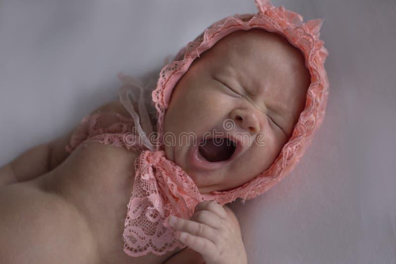 La ragazza di neonato in un cappuccio sbadiglia fotografie stock libere da diritti