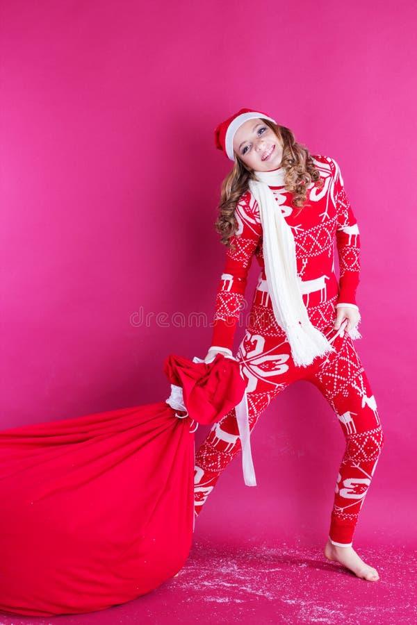 La ragazza di Santa sta tenendo la grande borsa rossa di natale immagine stock libera da diritti