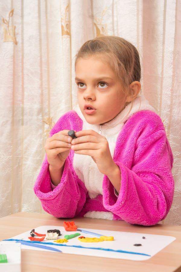La ragazza di sette anni guardata meditatamente si è impegnata nella modellistica del plasticine fotografia stock libera da diritti