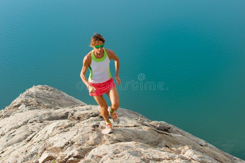 La ragazza di Skyrunner funziona su una parte posteriore pietrosa sopra un lago fotografie stock libere da diritti