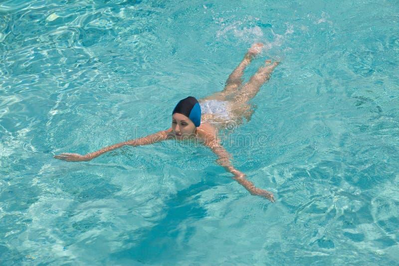 La ragazza di sport nuota in raggruppamento fotografia stock