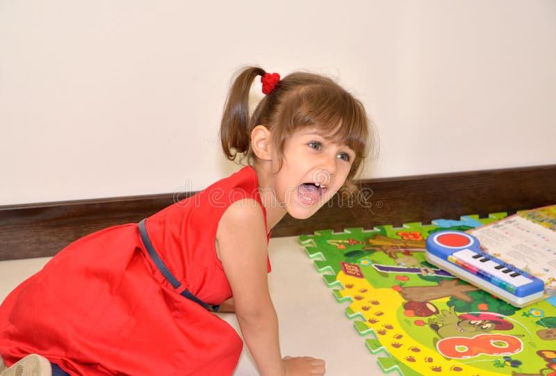 La ragazza di tre anni capricciosa grida, sedendosi su un pavimento fotografia stock libera da diritti