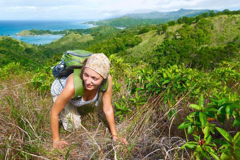 La ragazza di viaggio con lo zaino che fa un'escursione nelle montagne mette a fuoco sulla t fotografia stock libera da diritti