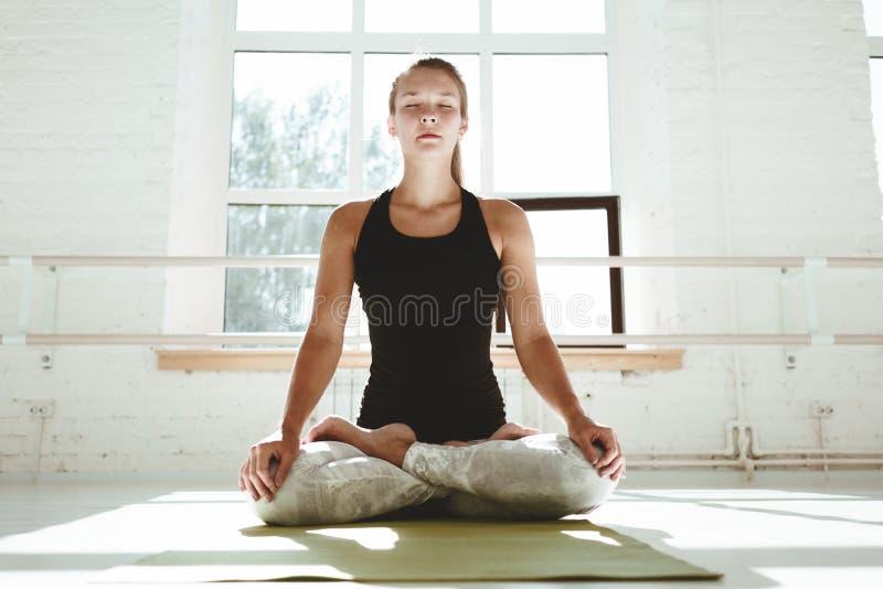 La ragazza di yoga esegue il asana Yoga di pratica della giovane donna felice in palestra soleggiata bianca presto che morking immagine stock libera da diritti