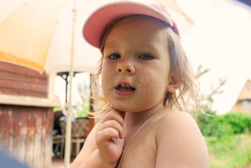 La ragazza dice qualcosa e tiene la sua mano vicino al mento fotografia stock libera da diritti