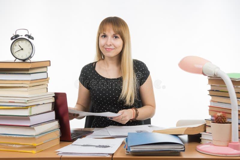 La ragazza dietro lo scrittorio ha sporcato i libri con un sorriso, tenente una carta fotografia stock