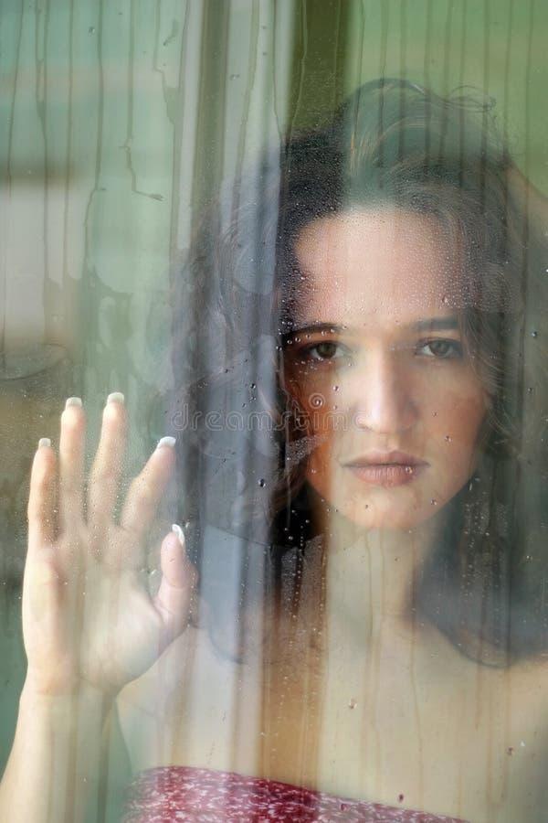 La ragazza dietro vetro immagine stock libera da diritti