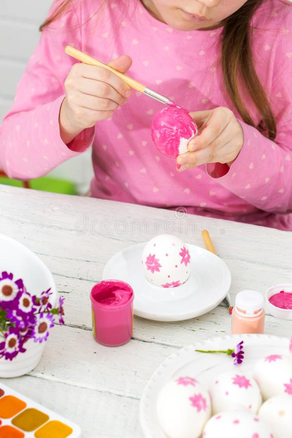 La ragazza dipinge le uova con una spazzola fotografia stock libera da diritti