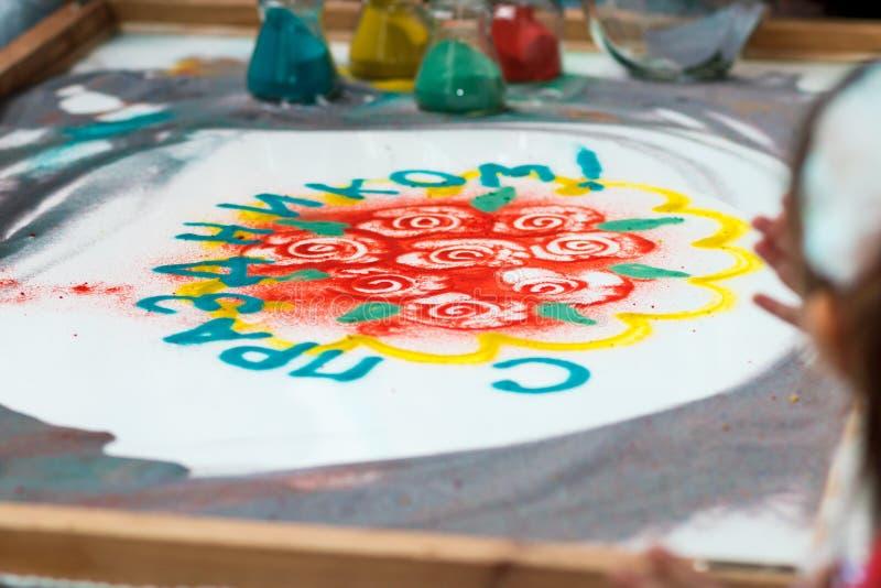 La ragazza disegna i fiori e il ` felice sulla sabbia, animazione di festa del ` di parola della sabbia, estraente il primo piano immagine stock libera da diritti