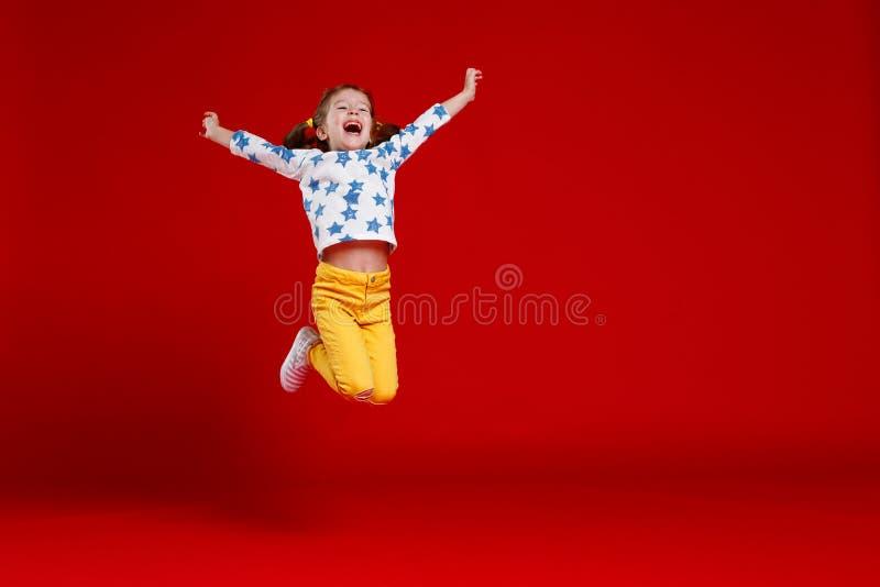 La ragazza divertente del bambino salta in vetri su fondo colorato immagine stock