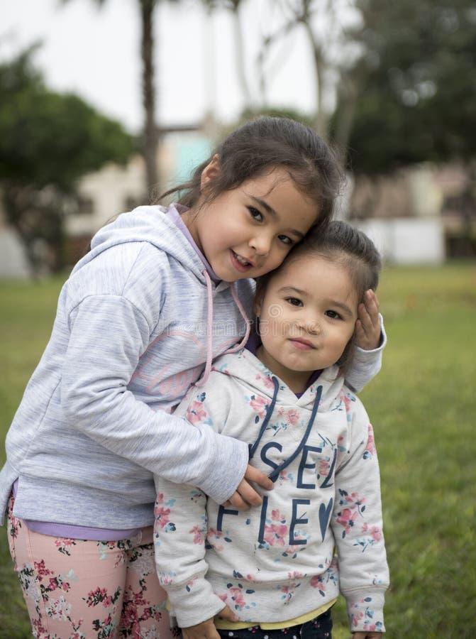La ragazza divertente felice gemella le sorelle che abbracciano e che ridono fotografie stock