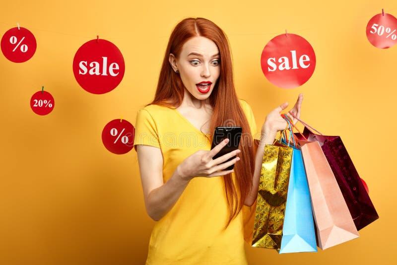 La ragazza divertente impressionante ha ricevuto un messaggio circa la grande vendita immagine stock libera da diritti