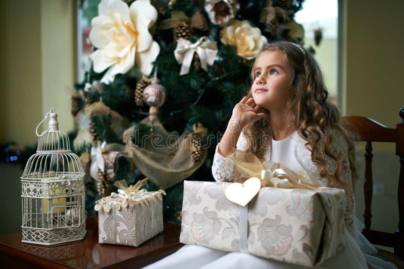 La ragazza dolce ha pensato la seduta con il regalo vicino all'albero di Natale immagini stock libere da diritti