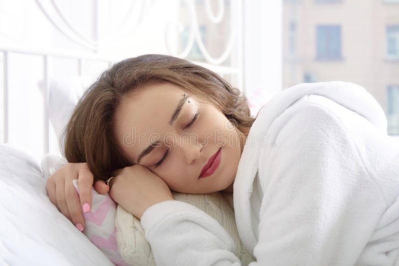 La ragazza dorme nel letto bianco di mattina fotografia stock libera da diritti