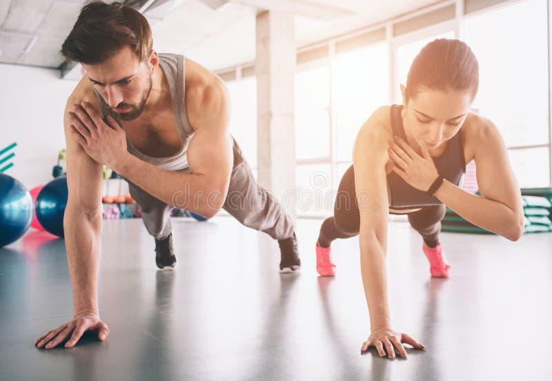 La ragazza e l'uomo forte esili stanno stando in una posizione della plancia della mano e stanno equilibrando su quella mano Semb immagine stock