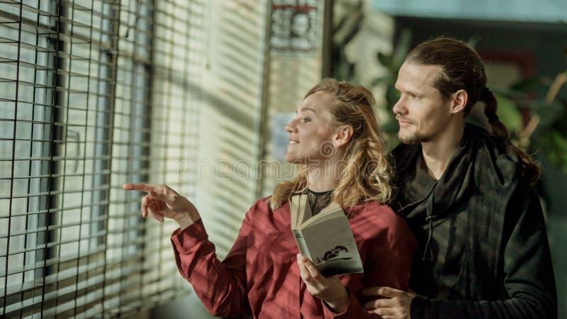 La ragazza e l'uomo vicino alla finestra, occhieggiano l'uomo che tiene la ragazza sulle spalle, relazioni sveglie, coppie nell'a fotografie stock libere da diritti
