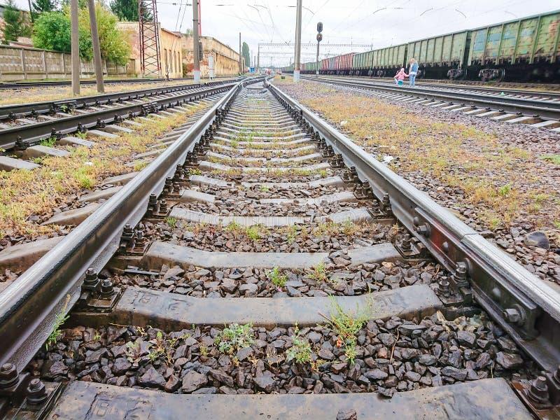 La ragazza e le strade ferrate dell'incrocio della madre Automobili di un treno merci Rotaie e traversine vicino alla stazione fe immagine stock libera da diritti