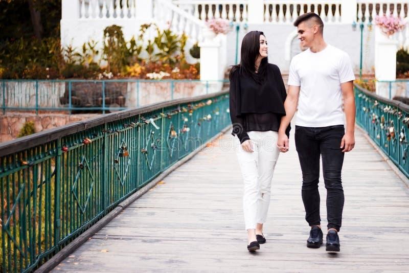 La ragazza e la passeggiata del tipo sul ponte nel parco immagine stock libera da diritti