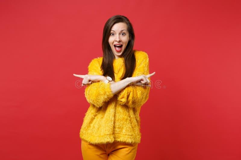 La ragazza eccitata in maglione giallo della pelliccia con tenersi per mano aperto della bocca ha attraversato indicare i dito in immagini stock