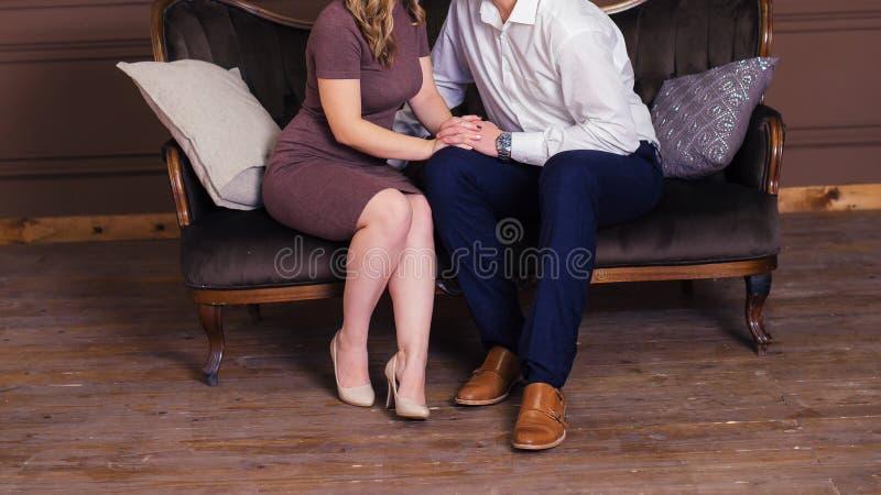 La ragazza ed il ragazzo nell'amore stanno sedendo su uno strato lussuoso dentro fotografia stock libera da diritti