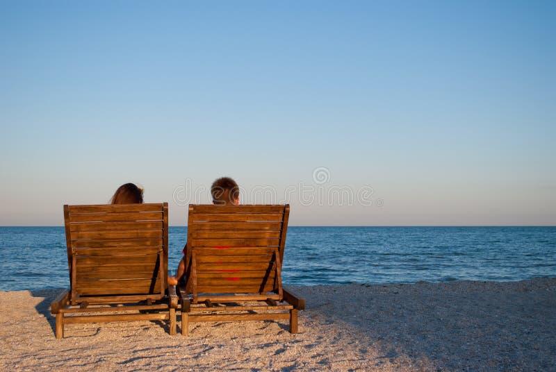 La ragazza ed il ragazzo romantici della data si siedono sulle sedie a sdraio di legno fotografia stock libera da diritti