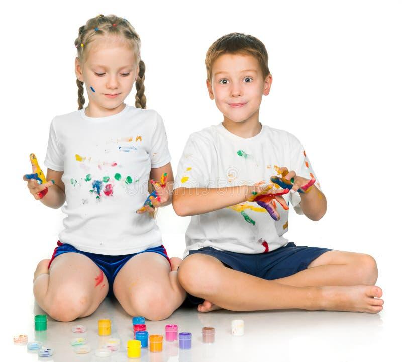 La ragazza ed il ragazzo stanno dipingendo fotografia stock