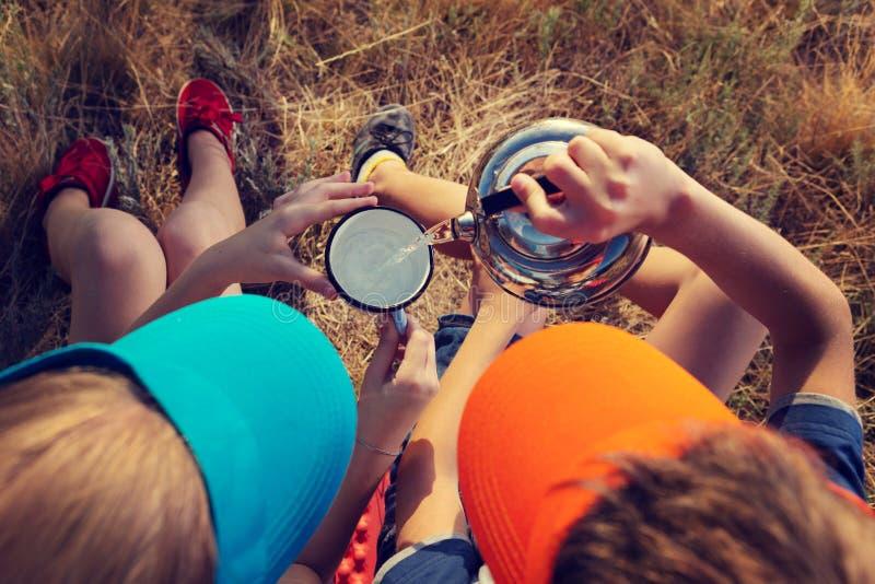 La ragazza ed il ragazzo in un aumento, si siedono sull'erba e l'acqua della bevanda, il ragazzo versa l'acqua in una tazza fotografie stock