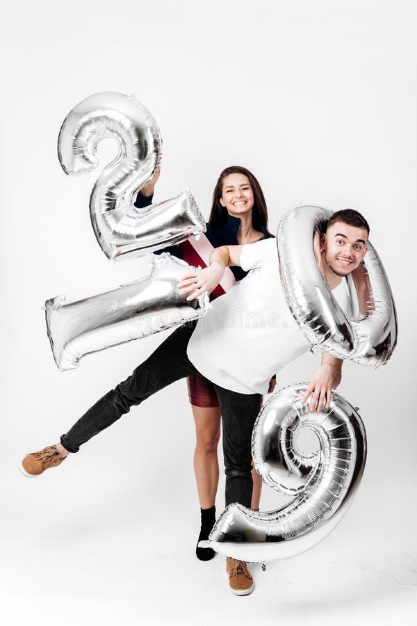 La ragazza ed il tipo vestiti in vestiti astuti alla moda stanno divertendo con i palloni sotto forma dei numeri 2019 su un bianc immagine stock
