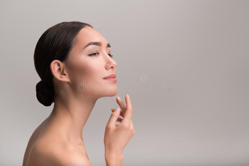 La ragazza elegante attraente sta dimostrando lo skincare perfetto immagine stock libera da diritti