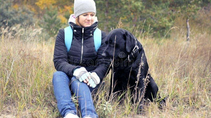 La ragazza esamina delicatamente il suo cane HD immagine stock libera da diritti