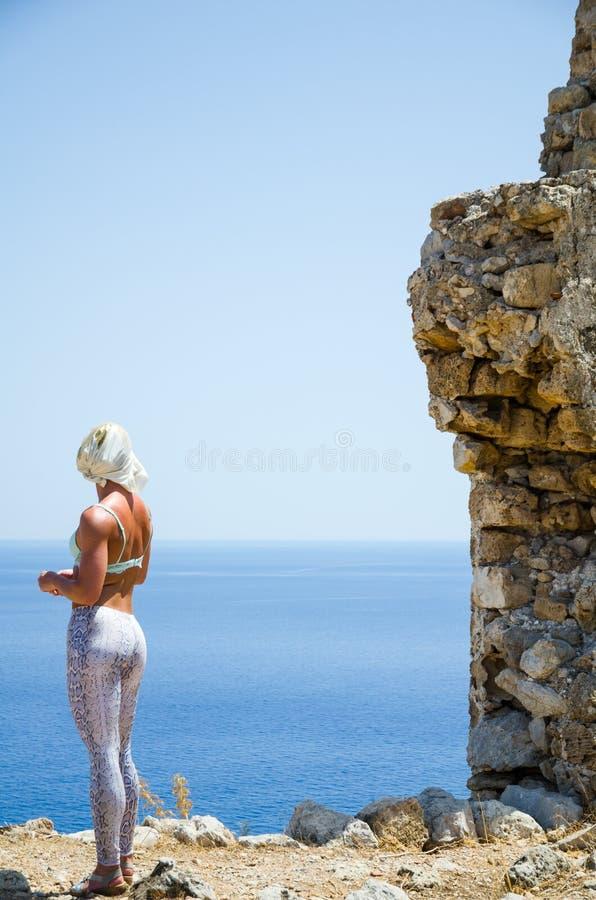 La ragazza esamina il mare da una scogliera fotografia stock libera da diritti