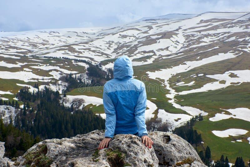 La ragazza esamina il plateau nevoso della montagna immagini stock libere da diritti