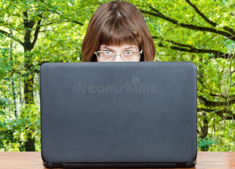 La ragazza esamina la copertura del computer portatile e della foresta verde immagini stock