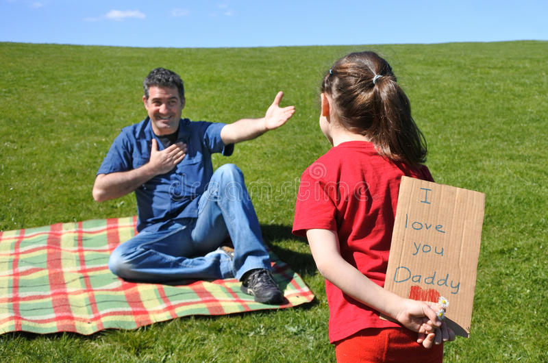 La ragazza esamina suo padre e tiene dietro lei indietro una carta immagini stock libere da diritti