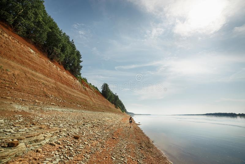 La ragazza esplora Rocky Banks ripido del fiume situato nella foresta di Taiga immagine stock libera da diritti