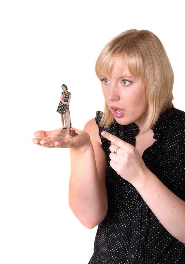 La ragazza estende la palma che tiene la piccola signora di pulizia immagini stock libere da diritti