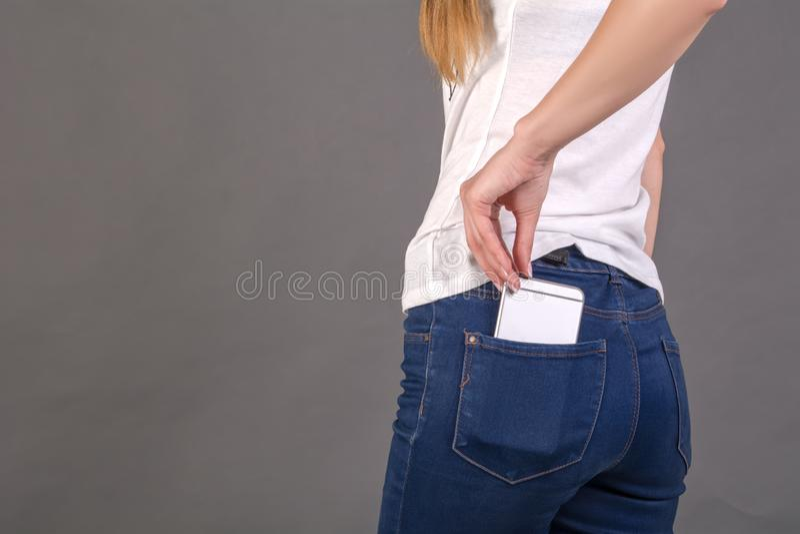 La ragazza estrae il telefono cellulare dalla tasca posteriore dei jeans immagine stock