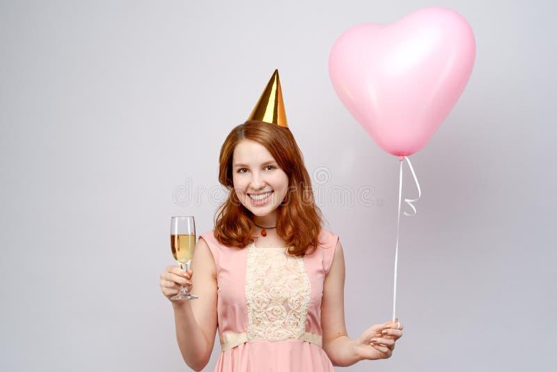 La ragazza europea adorabile con capelli rossi e un cappello festivo ampiamente che dà il benvenuto sorride Tiene in sue mani un  fotografia stock libera da diritti