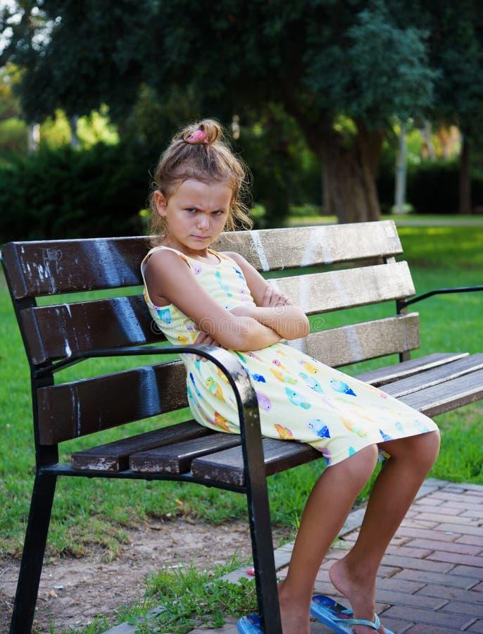 La ragazza eurupean abbastanza giovane che sembra arrabbiata o turbata sta sedendosi sul banco nel parco 2 fotografie stock