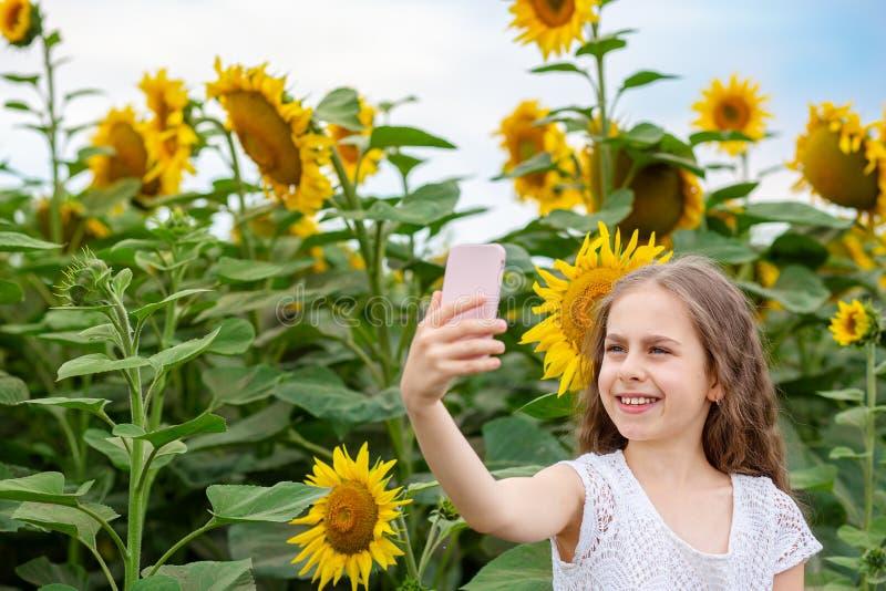 La ragazza fa il selfie su uno smartphone con un sorriso sul suo fronte, contro lo sfondo di un campo dei girasoli fotografia stock
