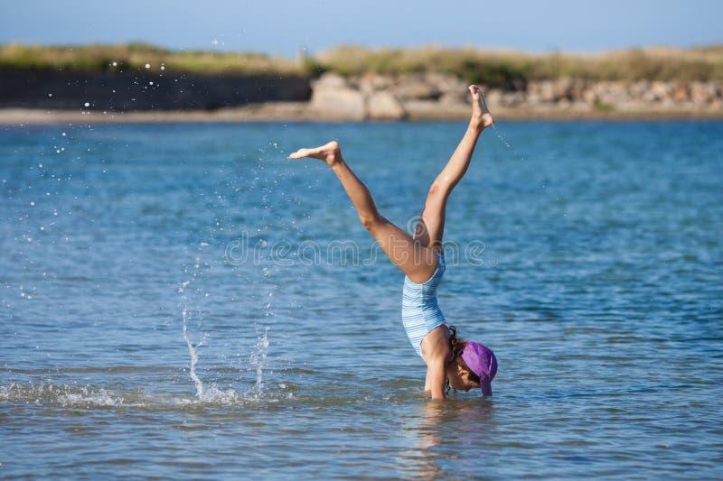 La ragazza fa un handstand nell'acqua di mare fotografia stock libera da diritti
