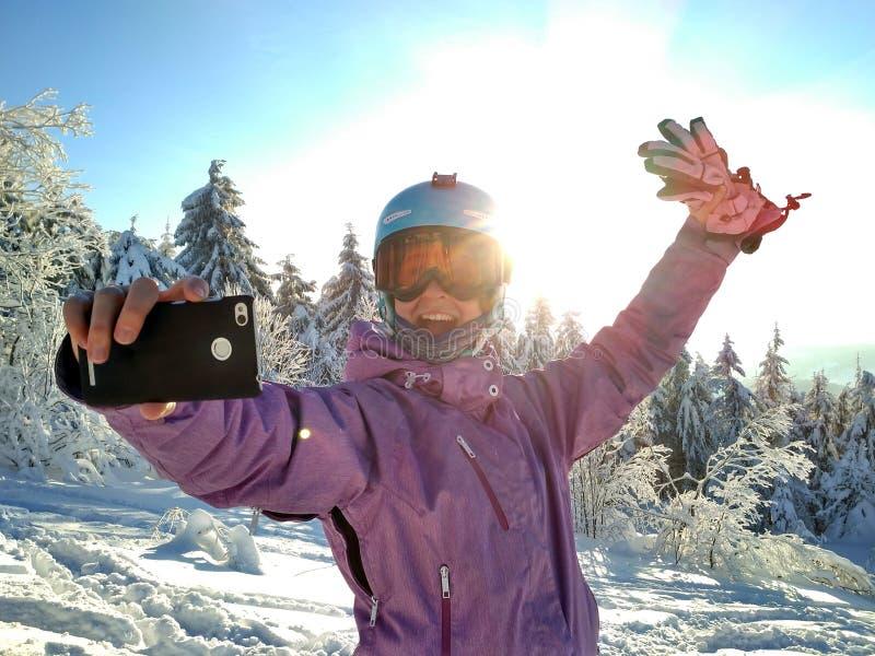 La ragazza fa un selfie in abbigliamento dello sci sulla montagna della neve fotografie stock